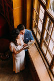 Young newlywed pair embracing in library near window. Charming bride leans to her handsome groom, holding book Royalty Free Stock Photos