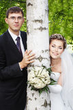 Young newlyweds and birch tree. Happy smiling bride with groom outdoors next to birch tree with blurred green leaves Stock Images