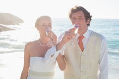 Young newlyweds drinking champagne linking arms Royalty Free Stock Image