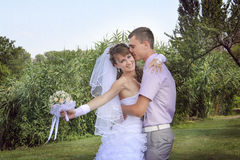 Young newlyweds embracing near river. Young newlyweds embracing and kissing near river Stock Photography