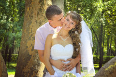 Young newlyweds embracing in the park Royalty Free Stock Photo