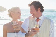 Young newlyweds having champagne linking arms Stock Photo