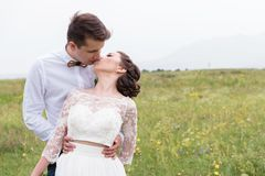 A couple of newlyweds standing in an arms embrace in nature Stock Photos