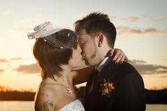 Young newlyweds kissing along riverbank Stock Image