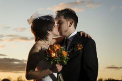 Young newlyweds kissing along riverbank. At sunset Stock Photography