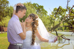 Young newlyweds looking to each other. Loving couple embracing on a riverside Stock Photos