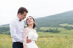 A couple of newlyweds standing in an arms embrace in nature Royalty Free Stock Images