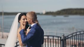 Young newlyweds standing in the quay in day of their wedding ceremony. Beautiful bride and groom enjoying each other. stock video footage