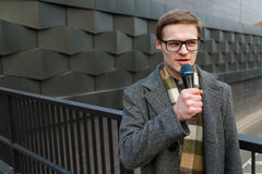 Young news reporter with microphone is broadcasting on the street. Fashion or business news. Royalty Free Stock Photography