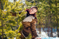 Young nice blond woman hold pine branches. Girl clothed shawl and sheepskin coat. Sunny winter day. National suit. Stock Image