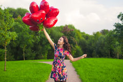 Young nice girl in beautiful dress with red balloons have fun outdoor royalty free stock images