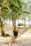 Young nice girl sitting barefoot on wicker hammock, sand and trees in background. stock photography