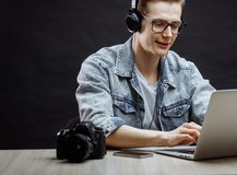 Young nice male typing message in the laptop. Young nice male in denim jacket and T-shirt typing message in the laptop Stock Photography