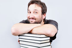 A young nice male is smiling on books Stock Photo
