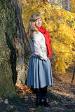 The young nice woman costs half-turned against the background of an autumn tree Royalty Free Stock Photos