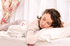 Young nice woman sleeping on white bed Stock Photos