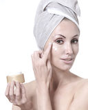 The young nice woman with a white towel on the head putting cosmetic cream on a face on a white background Stock Photography