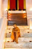 Young novice monk at Ayutthaya Province. Portrait young novice monk sitting in the staircase at old temple and many candle background, Ayutthaya Province royalty free stock photography