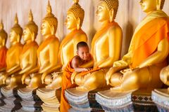 Young novice monk scrubbing buddha statue at old temple stock photography