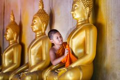 Young Novice monk scrubbing buddha statue at old temple royalty free stock image