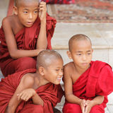 Young novice monks. OLD BAGAN, MYANMAR- OCT 15, 2013 : Group of unidentified young novice monks sitting down at Shwedagon Pagoda Temple, Myanmar on October 15 Stock Photo