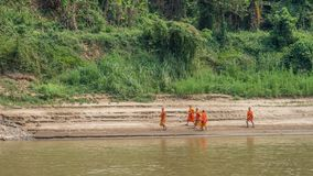 Young novice monks on river bank. Luang Phabang, Laos, Asia. Young novice monks on banks of the Mekong River. Slow boat cruise from Luang Prabang up the Mekong stock images