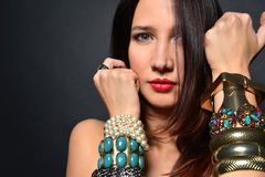 Young brunette lady with luxury accessories isolated on black background stock photos