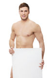 Young nude man covering his self with banner. Royalty Free Stock Photography