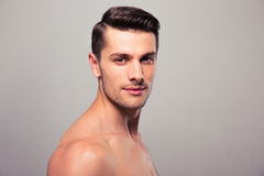 Young nude man looking at camera. Confident young man looking at camera over gray background Royalty Free Stock Photo