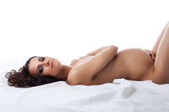 Young nude pregnant woman lay on white silk Stock Photography