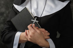 Young nun in a robe holding  bible and  cross against the dark wall. Close-up. Woman hugging  book Stock Image