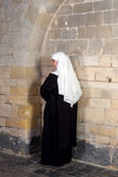 Young nun. Young sister or nun waiting against the walls of a 14th century church royalty free stock photography