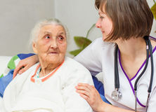 Young nurse caregiving an old lady lying in bed Royalty Free Stock Photos