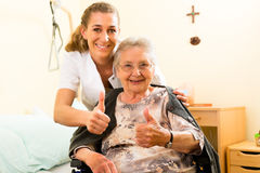 Young nurse and female senior in nursing home Royalty Free Stock Photo