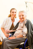 Young nurse and female senior in nursing home stock image