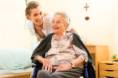 Young nurse and female senior in nursing home. The old lady sitting in a wheel chair Royalty Free Stock Image