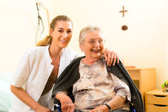 Young nurse and female senior in nursing home. The old lady sitting in a wheel chair Royalty Free Stock Photos