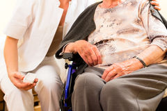 Young nurse and female senior in nursing home. The old lady sitting in a wheel chair stock photography