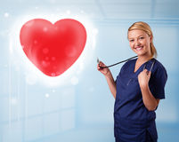 Young nurse healing a red heart Stock Photo