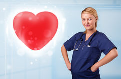 Young nurse healing a red heart Stock Images