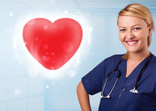 Young nurse healing a red heart Royalty Free Stock Photography