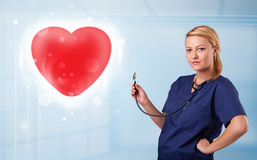 Young nurse healing a red heart Royalty Free Stock Image
