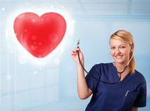 Young nurse healing a red heart Stock Image