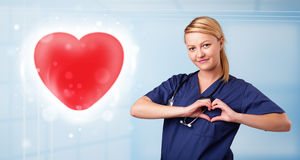 Young nurse healing a red heart Royalty Free Stock Photos