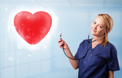 Young nurse healing a red heart Royalty Free Stock Images