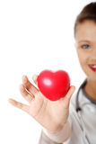 Young nurse with heart in her hand Stock Photos