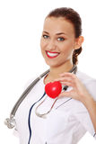 Young nurse with heart in her hand Royalty Free Stock Photo