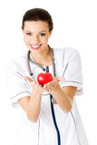 Young nurse with heart in her hand Royalty Free Stock Images