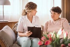 Nurse helping elderly lady with filling in the forms in the nursing home. Young nurse helping elderly lady with filling in the forms in the nursing home stock photo