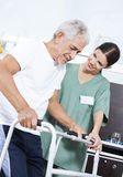 Young Nurse Helping Patient In Using Walker At Rehab Center. Young female nurse helping senior male patient in using walker at rehab center Stock Image